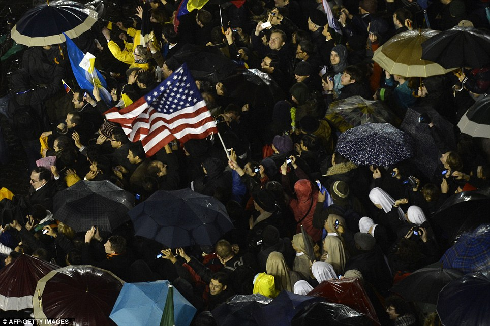 Ignoring the rain: Despite the grisly weather, those gathered waved flags and cheered as they awaited Benedict XVI's replacement