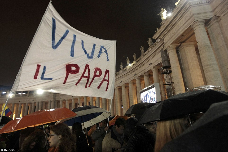 Show of faith: One Catholic stands with a sign reading 'Viva il Papa', translated as 'Long live the Pope'