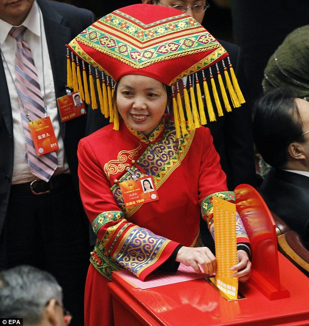 Colourful: An ethnic minority delegate in traditional dress casts her vote for president