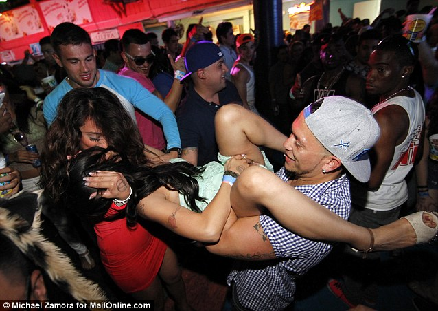 Clubs stay open till 2 a.m., making for a full day of partying which can lead to this scene of two girls kiss as one man holds one of them in mid-air as others look on