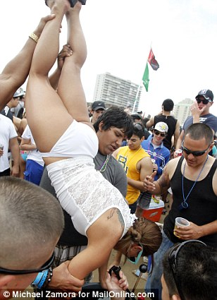 Beach goers help lift up a female reveler as she does a keg stand, drinking beer upside down straight from the tap