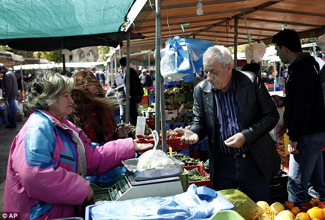 Spare change: People buy goods from a vegetable market in central Nicosia. The EU's economic affairs chief said there were now 'only hard choices left' for the latest casualty of the euro zone crisis