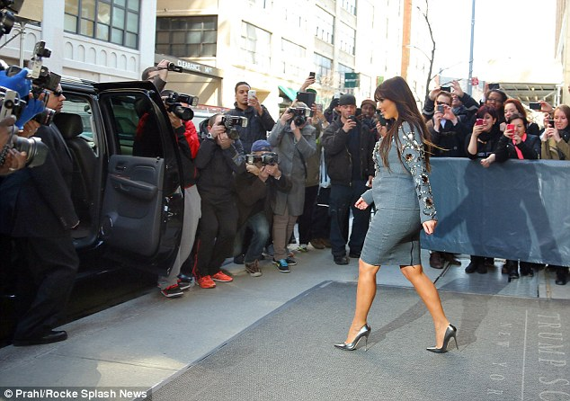 Woman of the moment: It was business as usual as Kim attracted a large crowd of photographers on her way out of the Trump Hotel