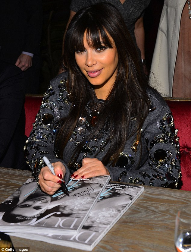 Leaving her stamp: The magazine held a luncheon in Kim's honour, seen here signing a copy of the magazine
