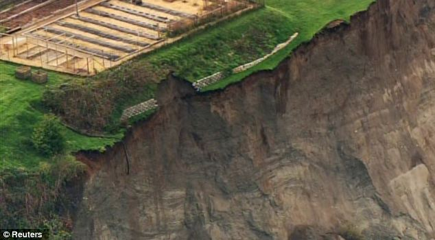 Teetering: A cliff is seen next to a yard following a landslide on Whidbey Island, Washington