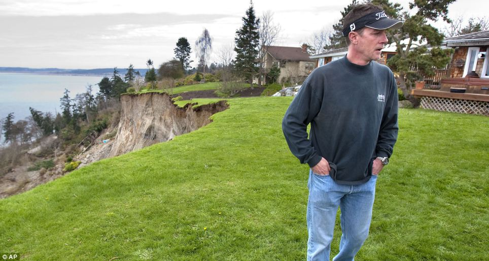 COncerns: Bret Holmes, who was evacuated from his home and lost 30 feet of his backyard, stands on top of the bluff on Whidbey Island near Coupeville