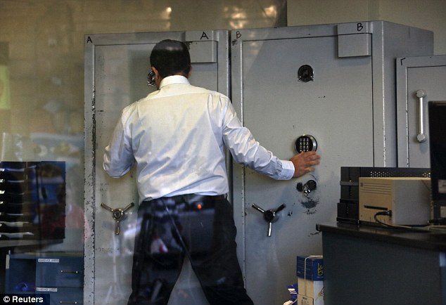 Tight controls: An employee opens a safe inside a Bank of Cyprus branch. Strict restrictions have been set on transactions to prevent a run on deposits once the banks open for six hours at noon (10am GMT)
