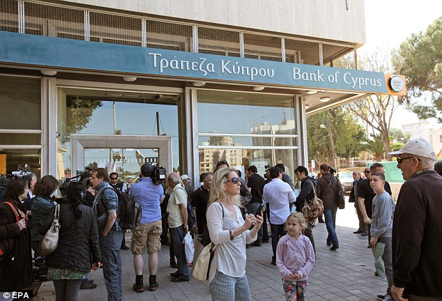 Ready for their readies: Customers queue anxiously outside a branch of the Bank of Cyprus, in Nicosia, Cyprus, as it prepared to open for the time in two weeks during the country's financial crisis