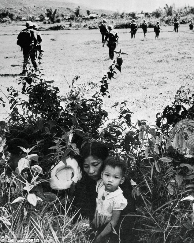 Fear: In this 15 May 1965 photo, a Vietnamese mother and her son hide in bushes near Le My to escape fighting as U.S. Marines go past after clearing the village of Viet Cong forces