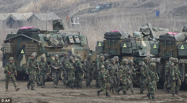 Troops: South Korean Marines during military drills today as it was revealed Chinese soldiers were amassing near the country's border with the North