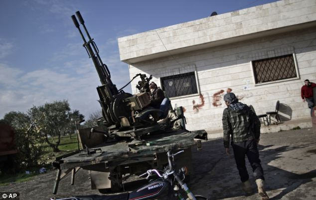 Pictured Syrian rebel checks an anti-aircraft weapon