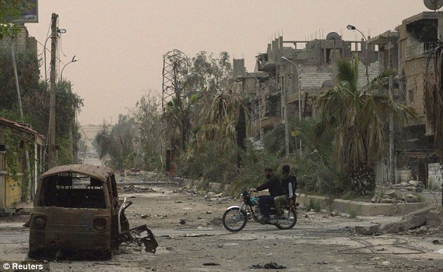 Road to nowhere: A motorcylist and passenger drive past the burnt-out wreckage of a car in Deir al-Zor