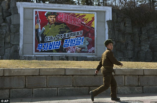 A North Korean soldier passes by roadside propaganda depicting a North Korean soldier killing a U.S. soldier in Pyongyang, North Korea today. The poster reads in Korean