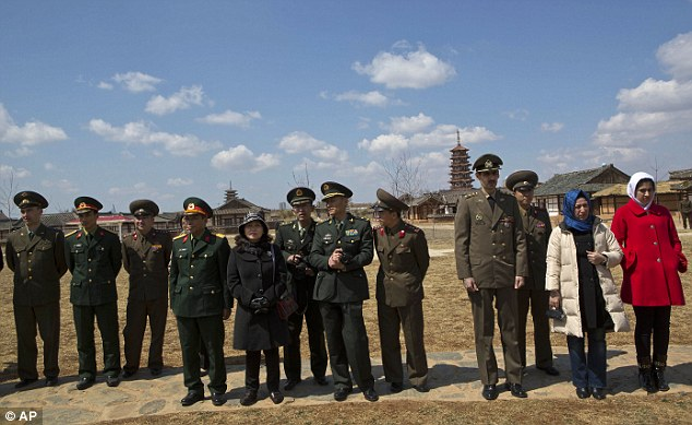 Still finding time to relax: North Korean military, along with foreign military attaches from Russia, China, and Iran watch a dance performance as they visit the Pyongyang Folk Park on the outskirts of the capital