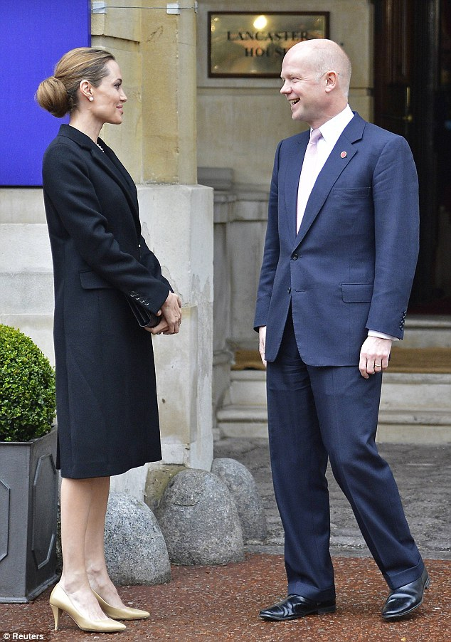 Actress Angelina Jolie is met by Britain's Foreign Secretary William Hague as she arrives for the G8 Foreign Ministers Meeting in central London