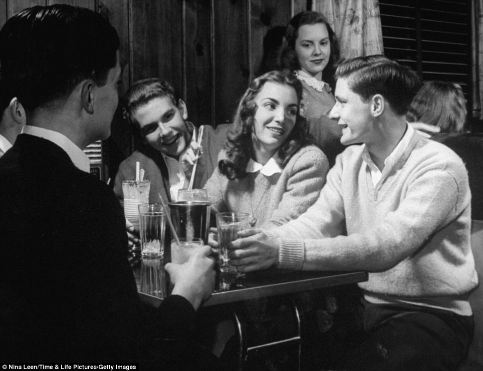Flirting: A young women flaunts her charm while sipping a milkshake with some teenage boys