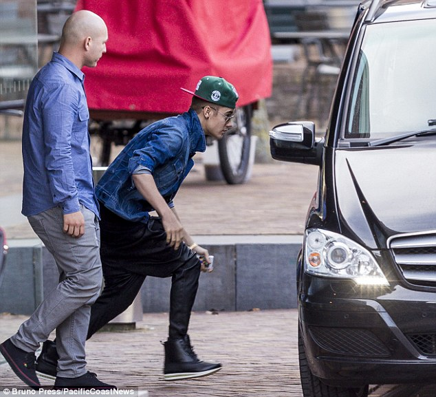 Sharp exit: Justin was leaving the Anne Frank House in Amsterdam on Saturday after writing a comment that has Facebook and Twitter fans outraged