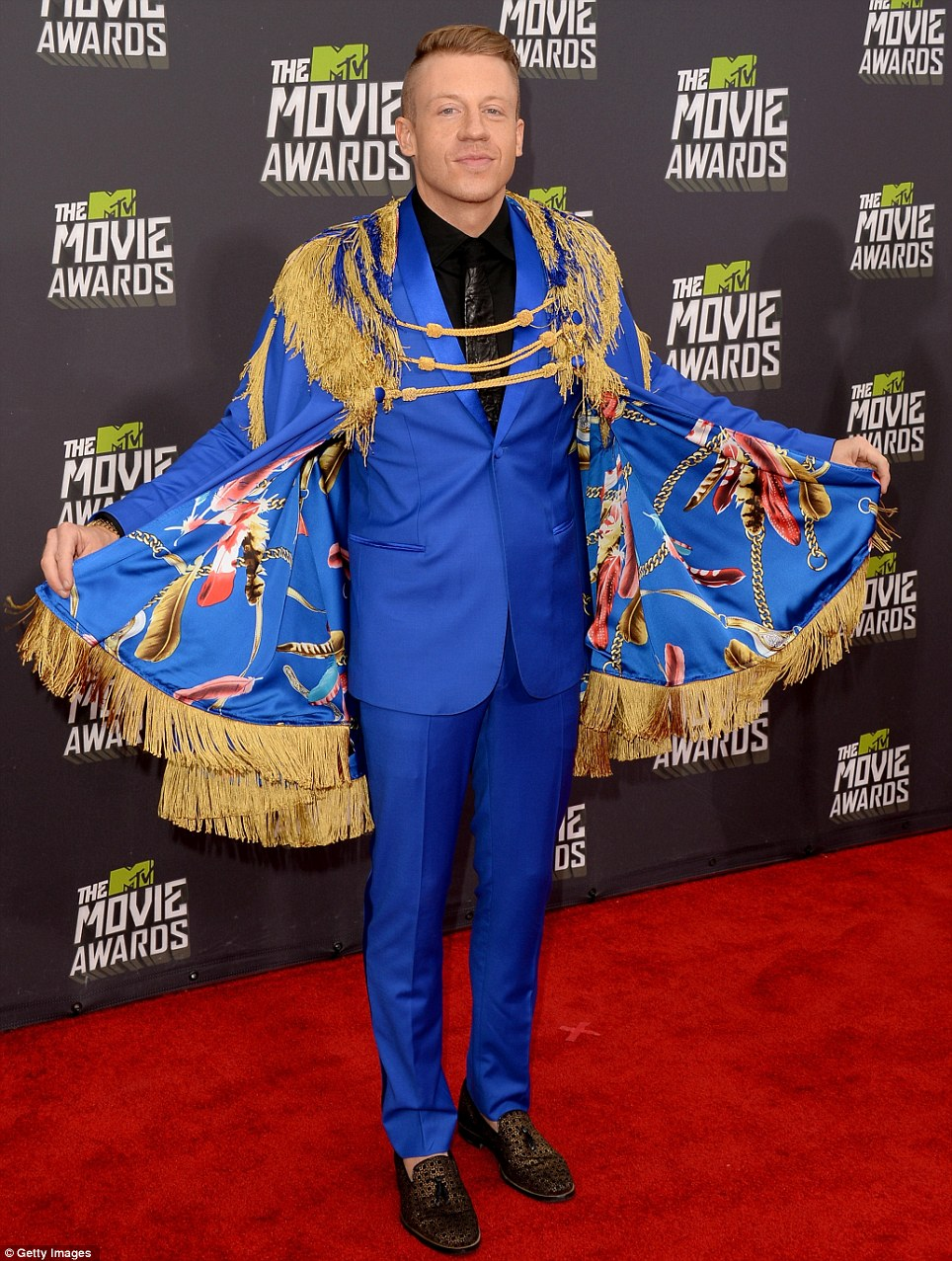 Unmatched: Macklemore rides high off his popular tune Thriftshop as he pairs a cape with a royal blue suit and a leather tie