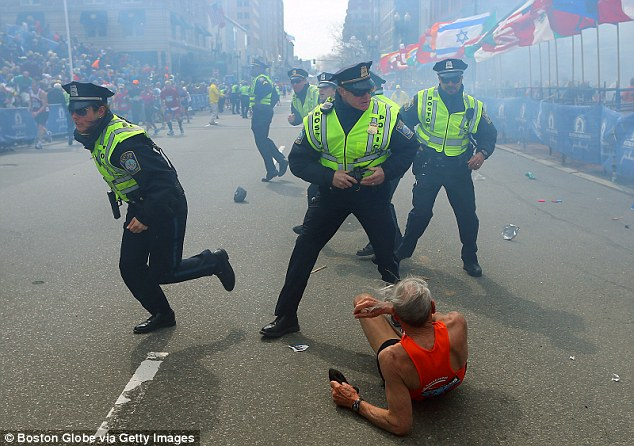 Impact: A runner, knocked to the ground by the blast, lies by police officers running to the scene