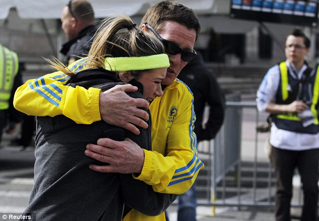 Struggle: A woman is comforted by a man near a triage tent set up for the Boston Marathon