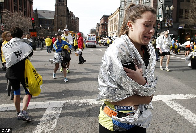 Sadness: An unidentified Boston Marathon runner leaves the course crying near Copley Square
