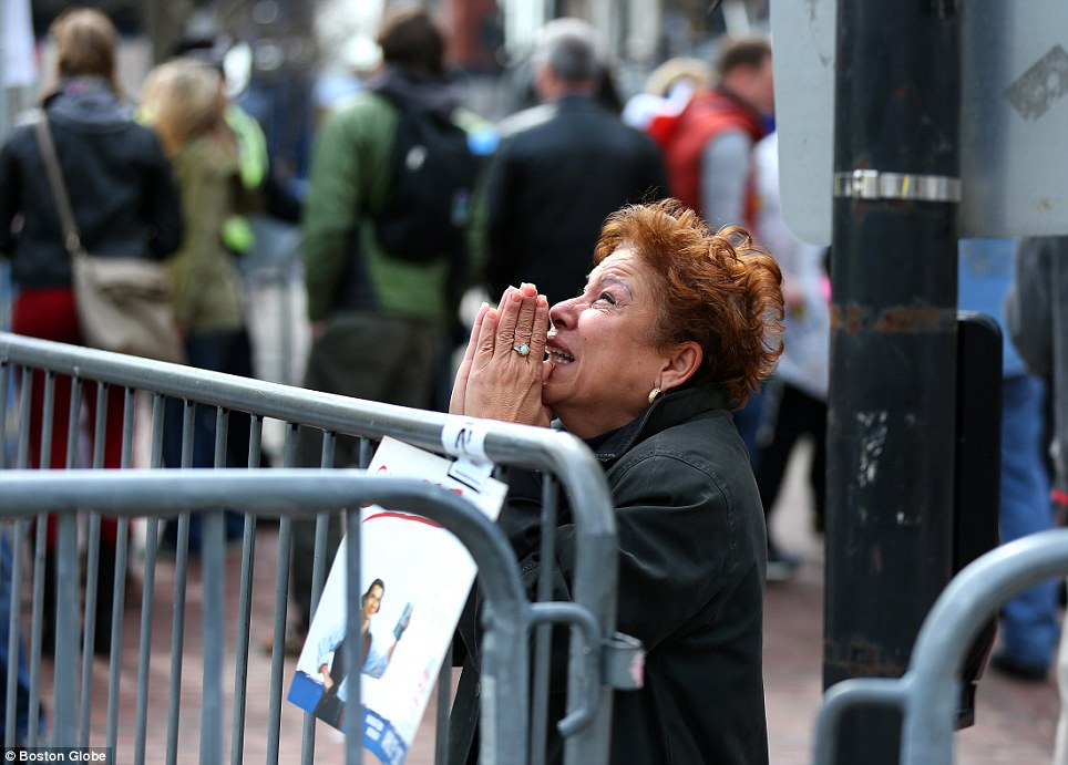 Looking to heaven: A woman kneels and prays at the scene of the first explosion in Boylston Street as the city comes to terms with the atrocity