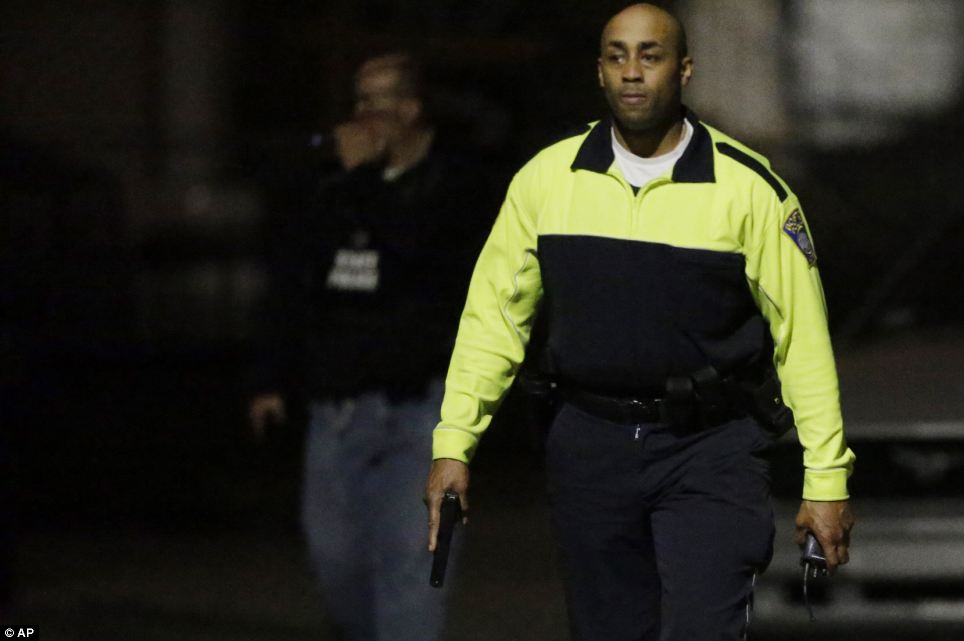 Hunt: Police officers with their weapons out search for a suspect on the streets of Watertown