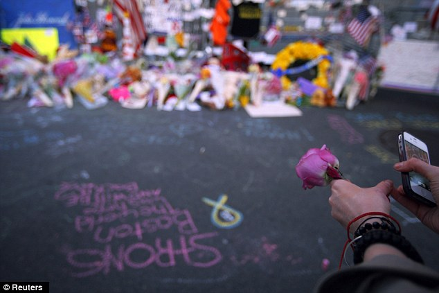 Flowers: A woman holds a flower at the memorial on Boylston Street last night