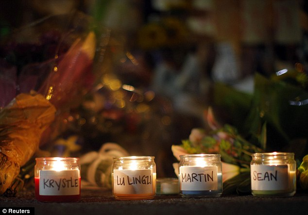 Memorial: Candles are lit for those who died in the Boston Marathon bombings and the subsequent police manhunt at a memorial on Boylston Street in Boston, Massachusetts April 21, 2013