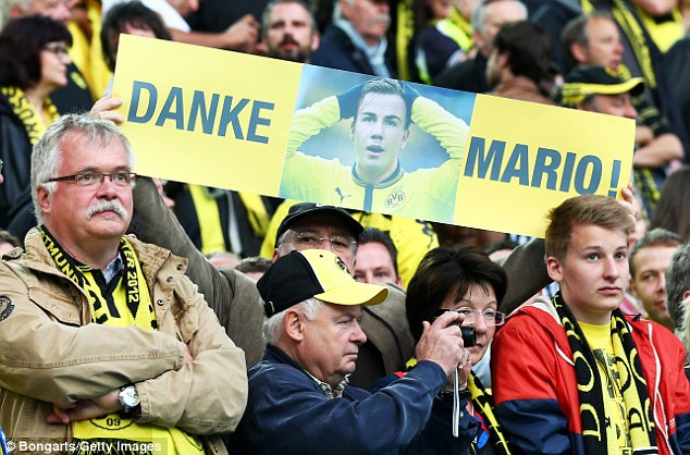 Minority: One fan holds a banner aloft saying thank you to the German international