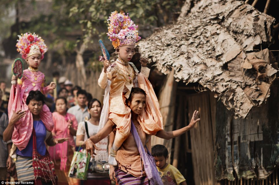 Children are carried around the streets on their parents' shoulders during the Ta Pwe celebrations at the Mae La refugee camp