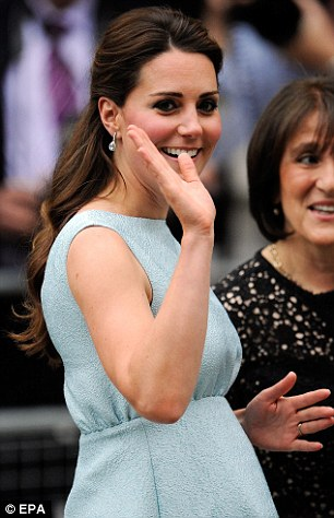 Waving to the crowds: The Duchess accessorised with diamond drop earrings