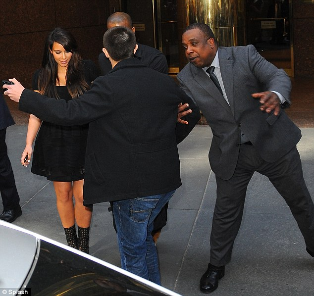 Photo time: The man was stopped by a bodyguard as he attempted to jump in front of the couple to take a picture of them