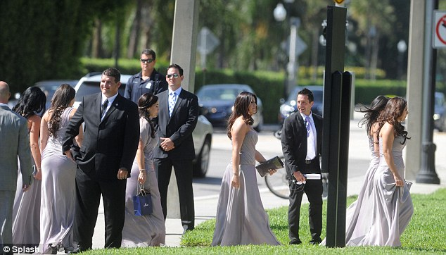 Dressed up: Wedding guests in matching dresses, accompanied by dark-suited dates, filed into the church for the exclusive ceremony