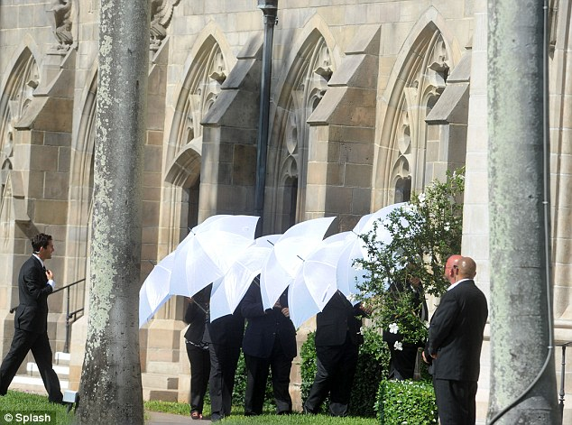 Security guards with white umbrellas concealed the lucky couple as they left the church - preventing fans and the press of seeing them