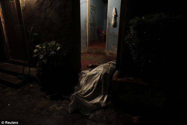 Carnage: The covered-up body of a man killed in a shoot-out between members of the Mara 18 street gang and police and military during an anti-drug operation lies in a house entrance in San Pedro Sula