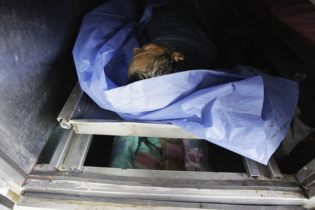 Shocking: The dead body of a man who died of gunshot wounds is seen at the morgue of a local hospital in San Pedro Sula last month