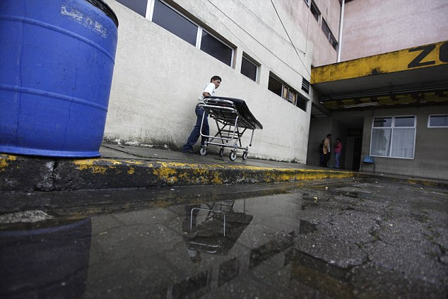 In constant use: A man pushes a stretcher after taking a body to the morgue