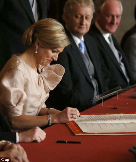 Queen Maxima, right, signs the Act of Abdication