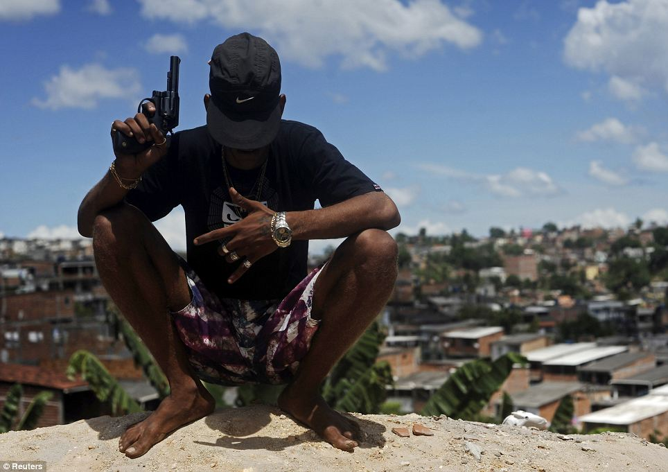 Whose streets? A Brazilian drug gang member nicknamed Firecracker, 22, poses with a gun atop a hill overlooking a slum in Salvador, Bahia State