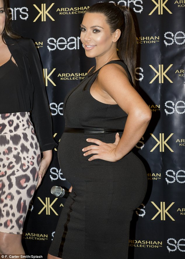 Kardashian kurves: Kim put her blossoming figure on display in a tight black dress in Houston, Texas on Saturday