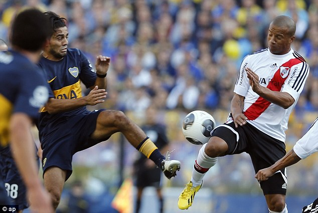 Physical: River's Carlos Sanchez (right) fights for the ball against Boca's Walter Erviti
