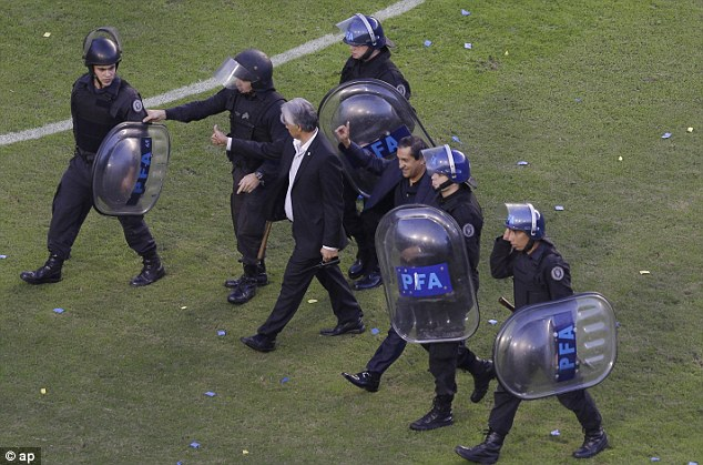 Protection: River Plate's coach Ramon Diaz is escorted off the field after a red card by riot police