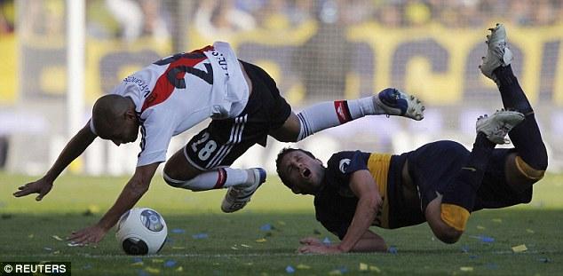 Foul: River Plate's Cristian Ledesma (left) crashes into Boca Juniors' Pablo Ledesma