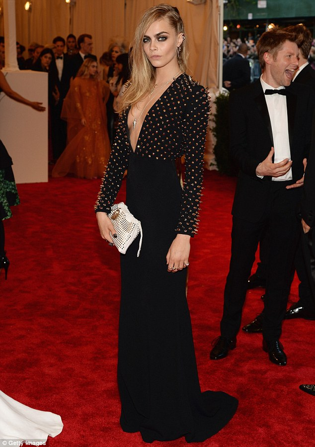 On par: Cara Delevigne honoured the evening's punk theme in a studded gown with a plunging neckline
