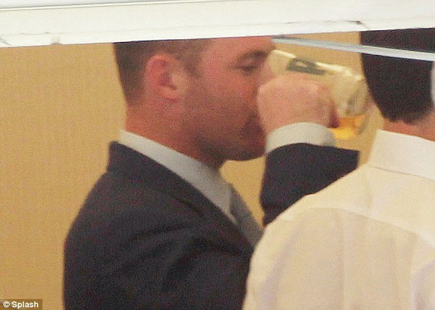 Beer we go: Rooney enjoys a pint at the races on Wednesday