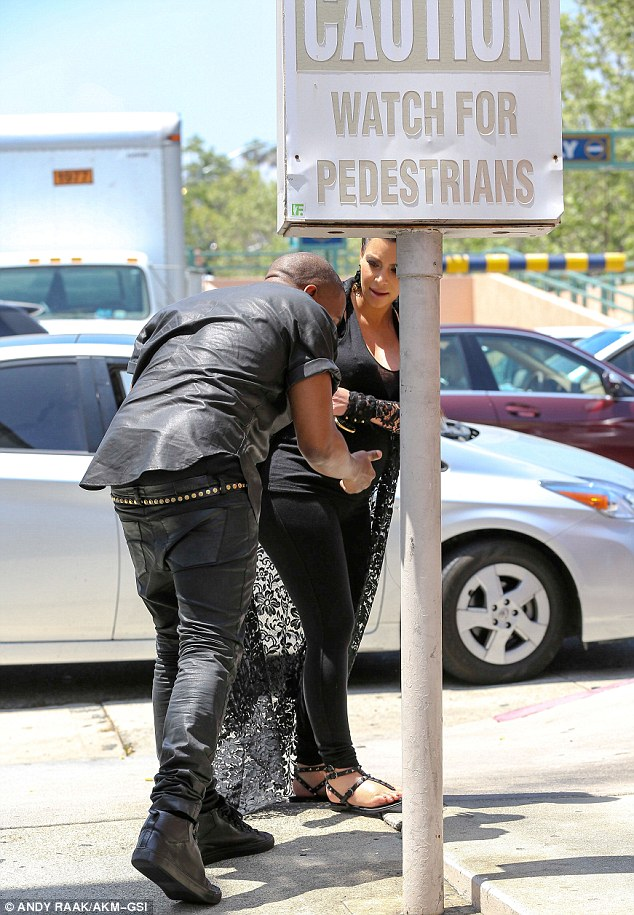 Ouch! Kanye hit his head on a sign that read 'Caution: Watch For Pedestrians'