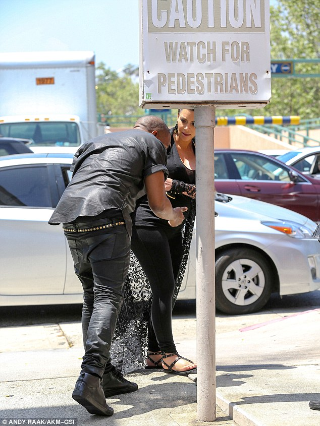 Are you ok? Kim looked on with concern after Kanye knocked his head on the signpost on Friday in Beverly Hills