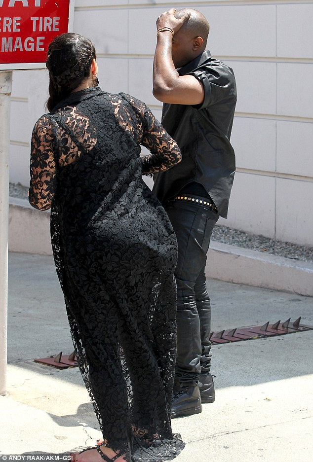 It hurts: Kanye clutched his head in pain as girlfriend Kim looked on with concern