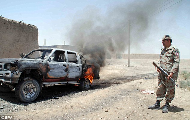 Restive: A paramilitary soldier stands beside a burning vehicle in the town of Chaman, where a shootout between the supporters of two candidates left six people dead